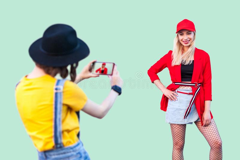 Vang het Ogenblik Twee modieuze hipstermeisjes in modieuze kleren die pret hebben samen, donkerbruine vrouw die beelden van haar  stock foto
