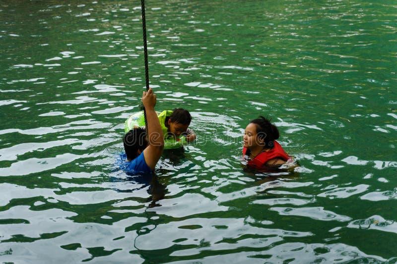 VANG VIENG, LAOS - 29 DE DEZEMBRO DE 2018: Os turistas apreciam nadar na lagoa azul, o ponto de turista natural famoso em Vang Vi fotografia de stock royalty free
