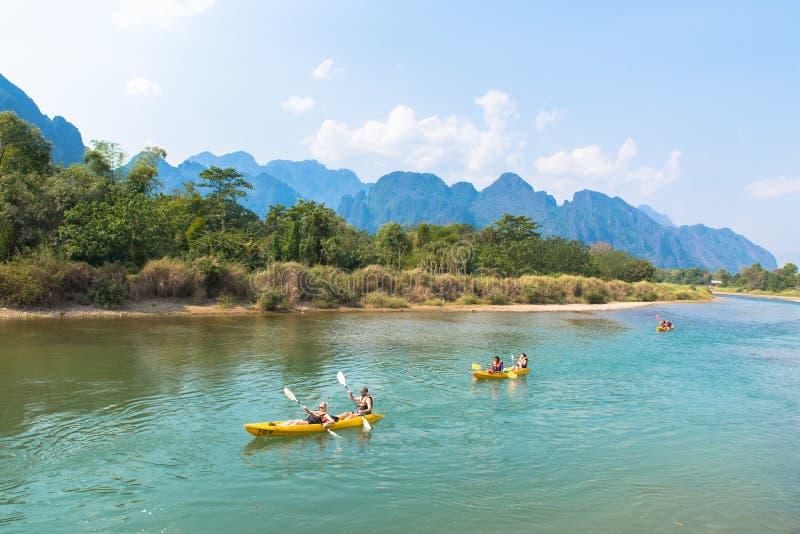 Vang Vieng, Laos - 17 de fevereiro de 2017: Turistas que kayaking em Nam S imagens de stock royalty free