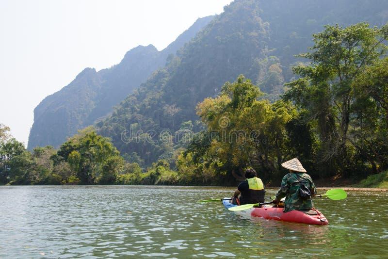 Vang Vieng, Laos - 16 de fevereiro de 2016: Os turistas não identificados estão enfileirando barcos do caiaque no rio da música o foto de stock