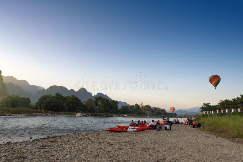 Hot air balloons flying over Nam Song River and tourist kayaks in Vang Vieng, popular resort town in Lao PDR. Vang Vieng, Laos - November 2015: Hot air balloons royalty free stock images