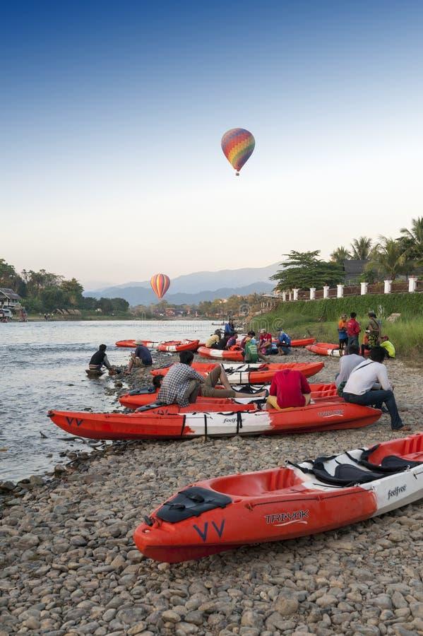 Hot air balloons flying over Nam Song River and tourist kayaks in Vang Vieng, popular resort town in Lao PDR. Vang Vieng, Laos - November 2015: Hot air balloons stock photography
