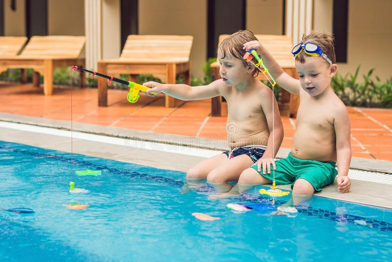 Vangt kleine leuke jongen twee een stuk speelgoed vis in de pool royalty-vrije stock fotografie
