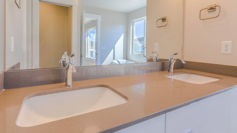 Vanidad del fregadero doble del panorama dentro del cuarto de baño moderno de una nueva casa fotografía de archivo libre de regalías