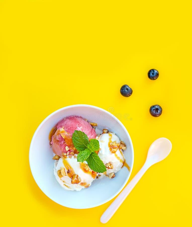 Vanila和草莓冰淇凌用焦糖和薄菏在白色碗有坚果和蓝莓的在黄色背景 三个瓢, 免版税库存照片