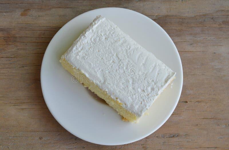 Vaniljanstrykning mjölkar den kräm- kakan på maträtt royaltyfri bild