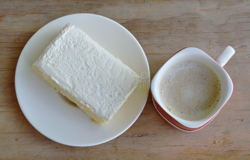 Vaniljanstrykning mjölkar den kräm- kakan på maträtt och kaffe royaltyfri bild