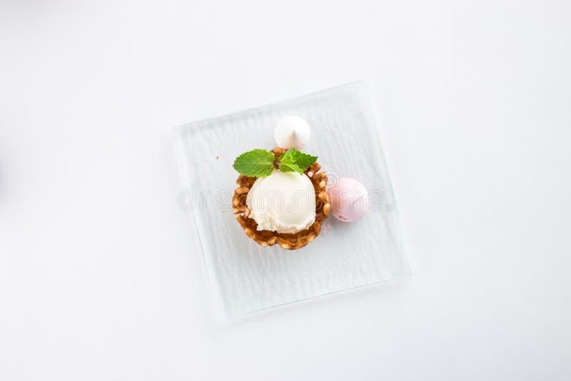 Vaniljglass med meringe och mintkaramell i en rånbunke som isoleras på vit bakgrund arkivbilder