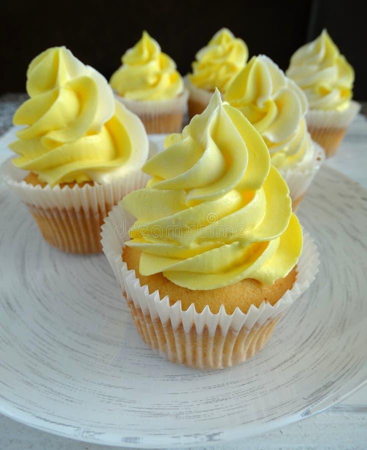 vaniljmuffin med citrondriftstopp och gul kräm arkivbild