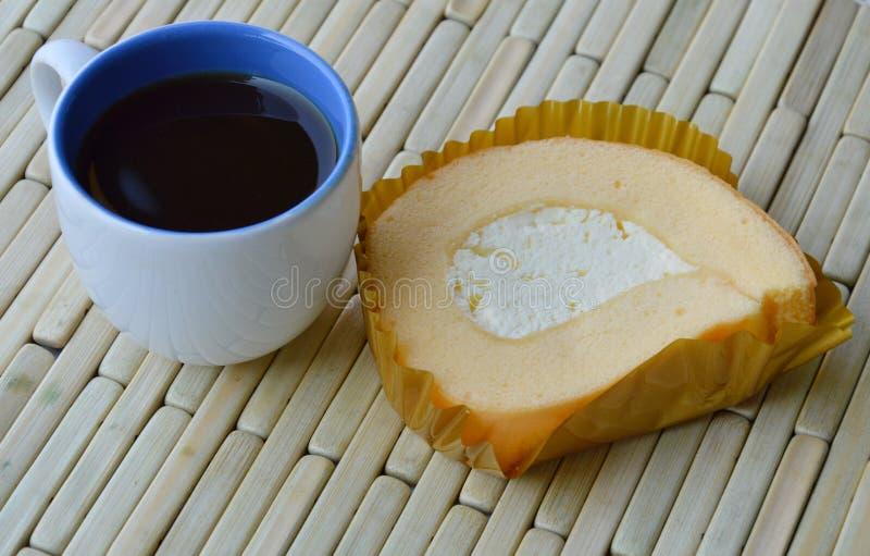 Vaniljrullkaka med koppen för ny kräm och för svart kaffe arkivbilder