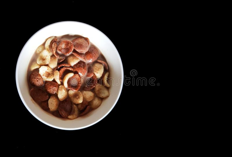Vanilla and chocolate cornflakes dipped in chocolate milk in a white bowl in black background stock image