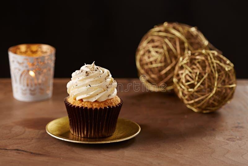 Vanilla cupcake on Christmas background. Vanilla cupcake on black Christmas background royalty free stock photo