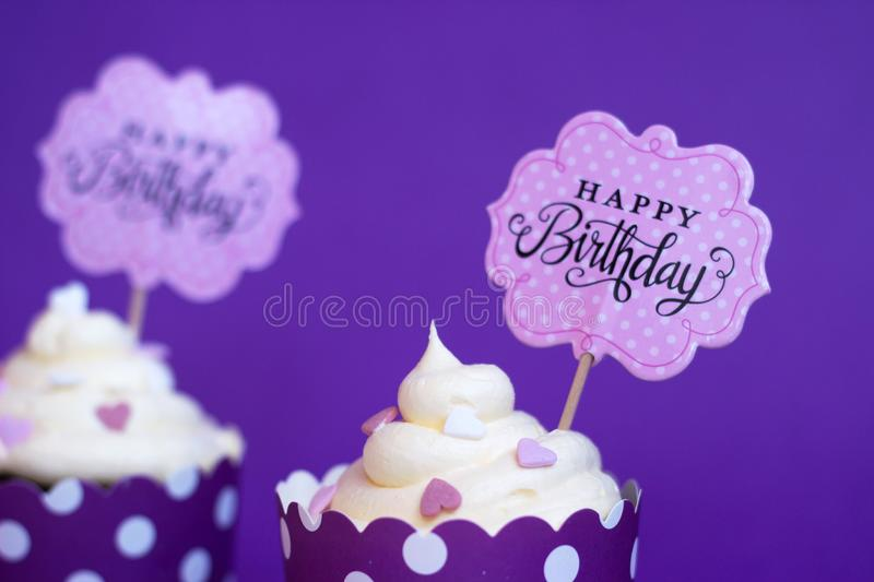 Vanilla cupcakes with small decorative hearts and happy birthday. Sign, against violet background; party background royalty free stock images