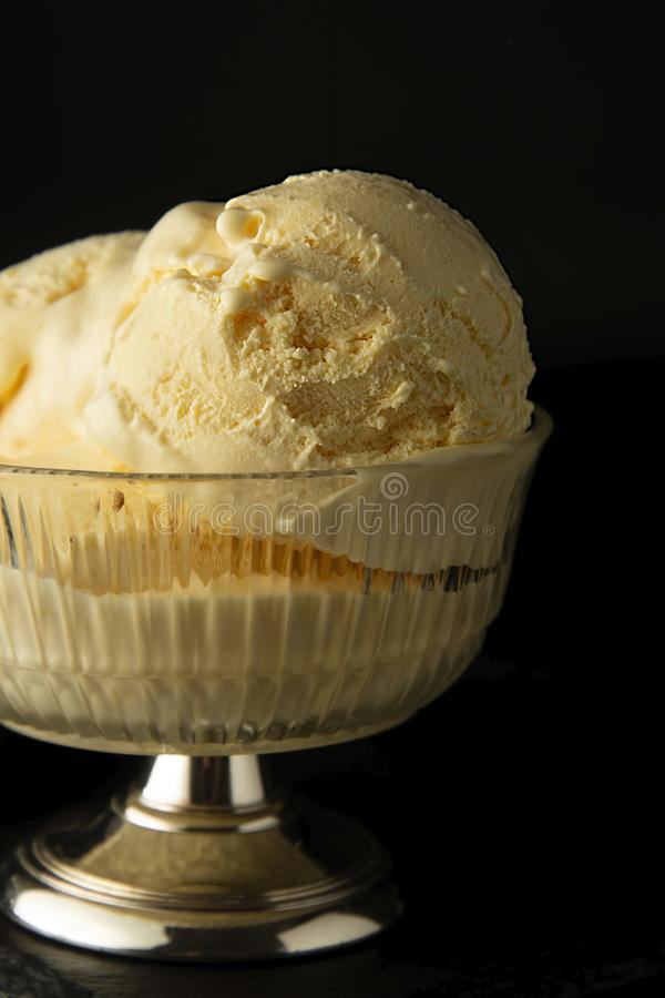 Vanilla Ice Cream scoops in glass elengant cup. Isoalted over black background with copy space. Summer, refreshing ice cream. Homemade Organic Vanilla Ice Cream royalty free stock images