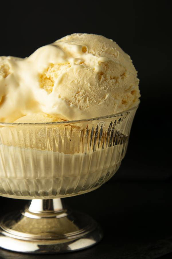 Vanilla Ice Cream scoops in glass elengant cup. Isoalted over black background with copy space. Summer, refreshing ice cream. Homemade Organic Vanilla Ice Cream royalty free stock photography