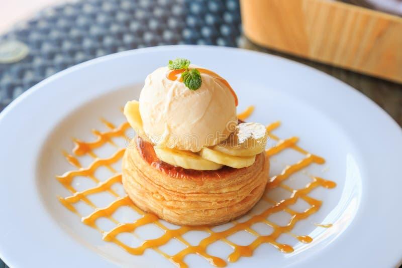 Vanilla icecream, banana and crispy tart with caramel syrup. Vanilla ice cream, banana and crispy tart with caramel syrup in the white plate royalty free stock photos