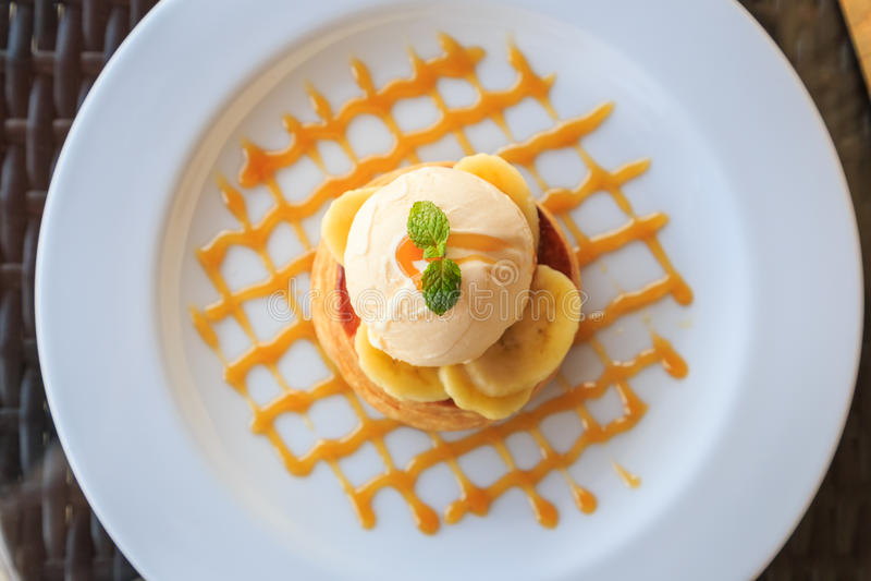Vanilla icecream, banana and crispy tart with caramel syrup. Topview of vanilla icecream, banana and crispy tart with caramel syrup stock photo