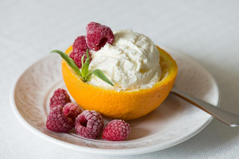 Vanilla Icecream with raspberry, summer dessert. Delicious sunday scoop in an orange half on a white plate stock photography