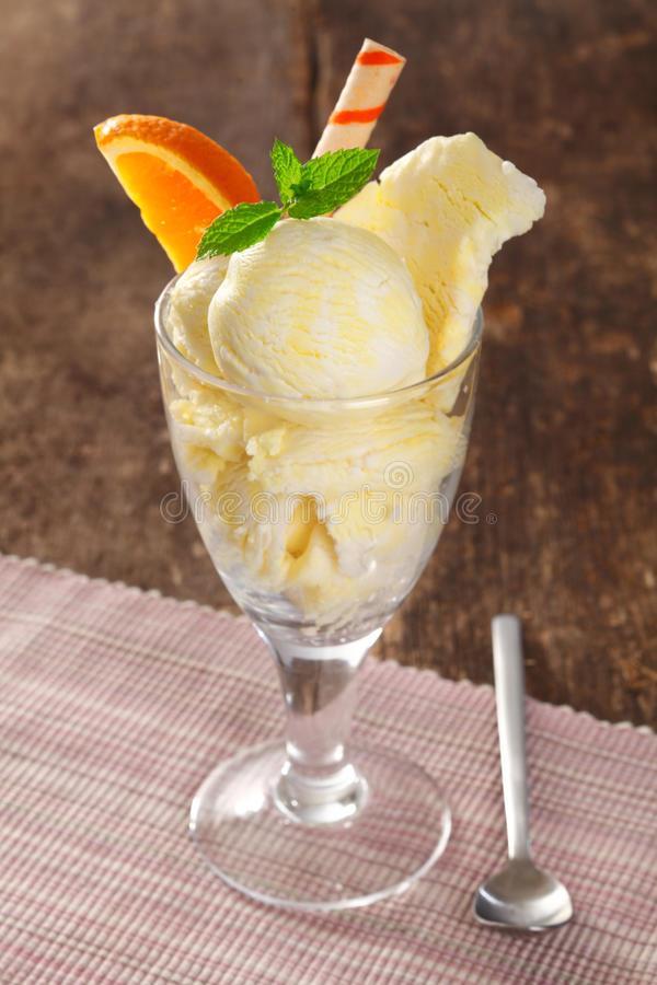 Vanilla icecream in a tall glass. Cold creamy vanilla icecream in a tall glass garnished with mint and orange and a spiral wafer royalty free stock photography