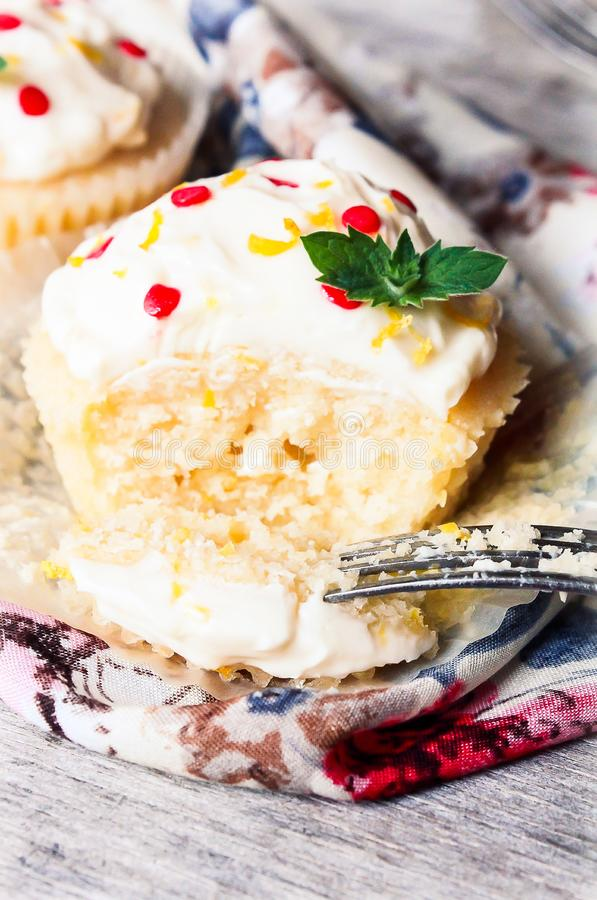 Vanilla lemon cupcakes with mascarpone cream cheese decorated with freshly grated lemon zest, sugar and fresh mint leaves, selecti stock images
