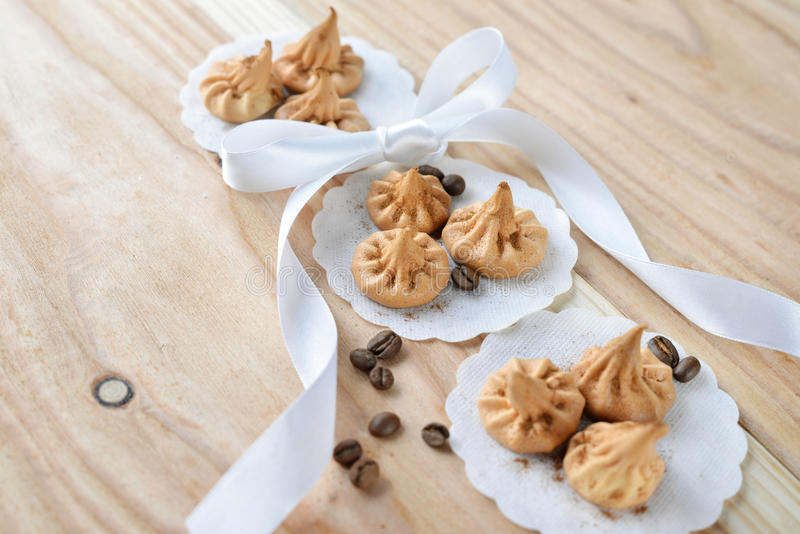 Vanilla meringue cookies on wooden background. With copy space. Cakes with white ribbon and coffee stock photography