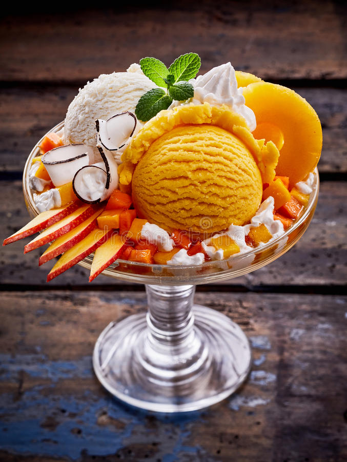 Vanilla and Peach Ice Cream Sundae with Fruit. High Angle Close Up View of Sundae Made with Scoops of Vanilla and Peach Flavored Ice Cream, Slices of Fresh Fruit royalty free stock photo