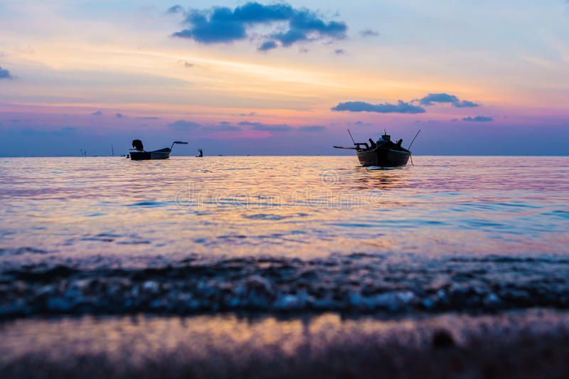 Vanilla romantic seascape at sunset. Seething wave of calm beautiful sunset with fishing boats on the island paradise of Koh Phangan in Thailand. Boats rest royalty free stock images