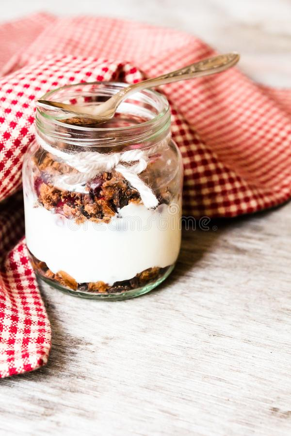 Vanilla yogurt dessert with chocolate cookies and fresh cherry. In a jar on a wooden table, selective focus royalty free stock photos