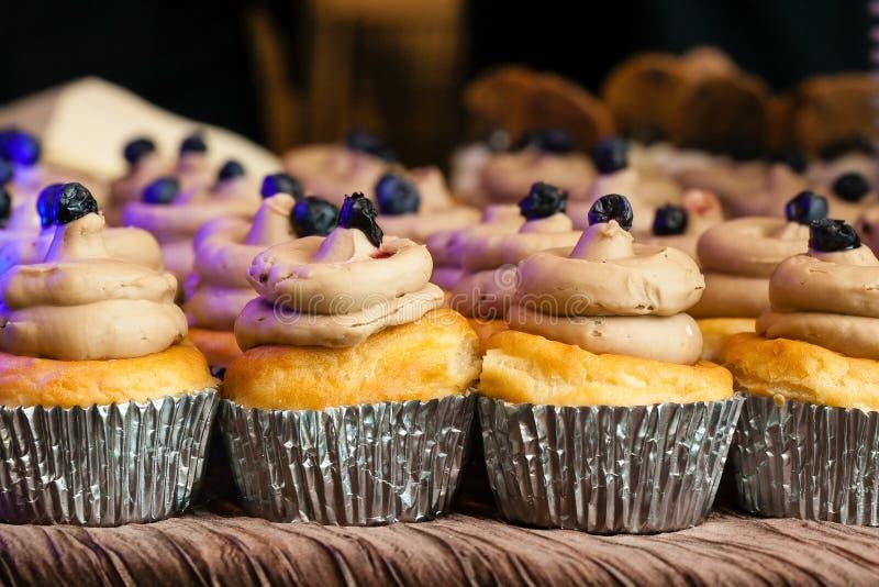 Vanille épousant des petits gâteaux avec le givrage crème dans des tasses d'aluminium pendant un événement approvisionné image stock