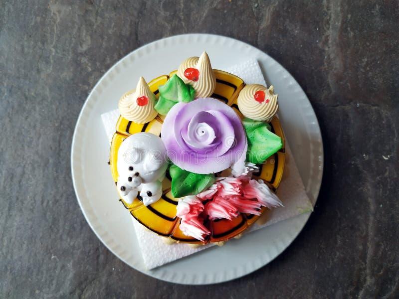 Vanille buttercream Geburtstagskuchen mit buntem bespr?ht ?ber einem neutralen Hintergrund lizenzfreies stockbild