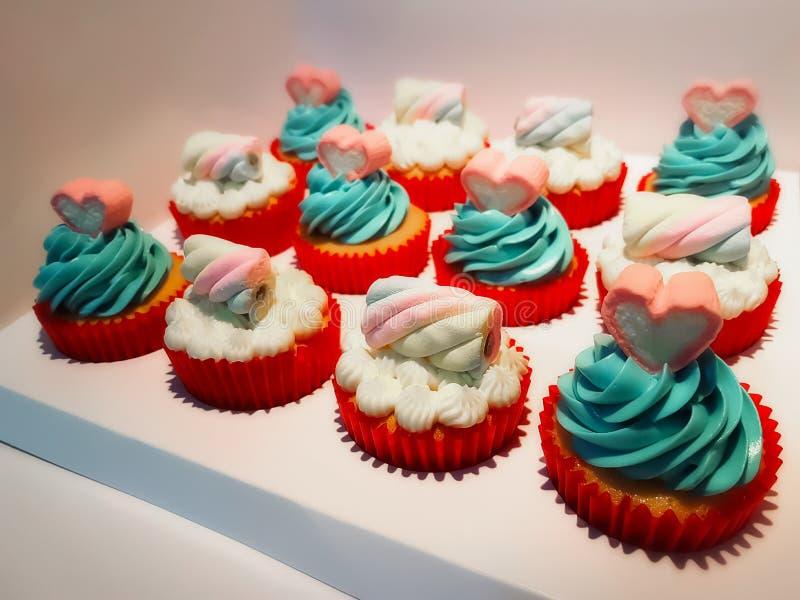 Vanille cupcakes in rode koppen die met kleurrijke room en mashmelo op bovenkant worden verfraaid stock fotografie