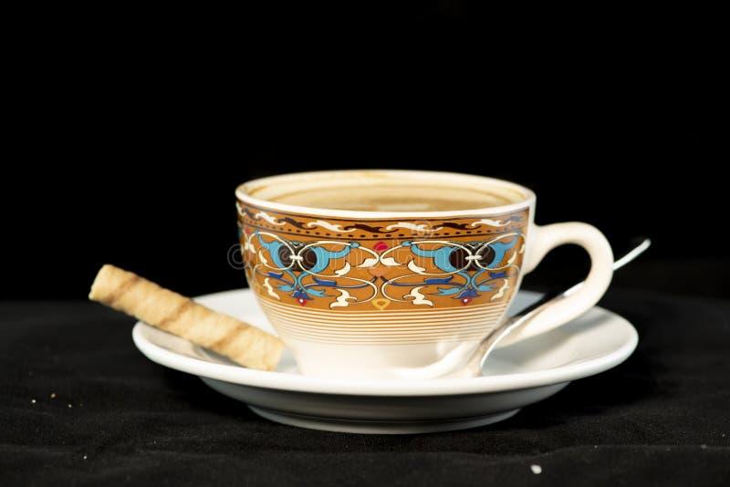 Vanille Lattekaffee mit Oblatenrollen mit lokalisiertem schwarzem Hintergrund lizenzfreie stockfotografie