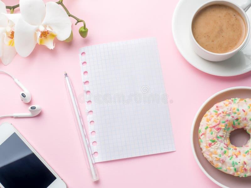 Vanille plate de joueur de crayon de bloc-notes d'orchidée de beignet de tasse de café de configuration sur un fond rose photos libres de droits