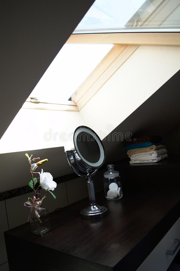 Vanity table with round mirror under a skylight stock photo