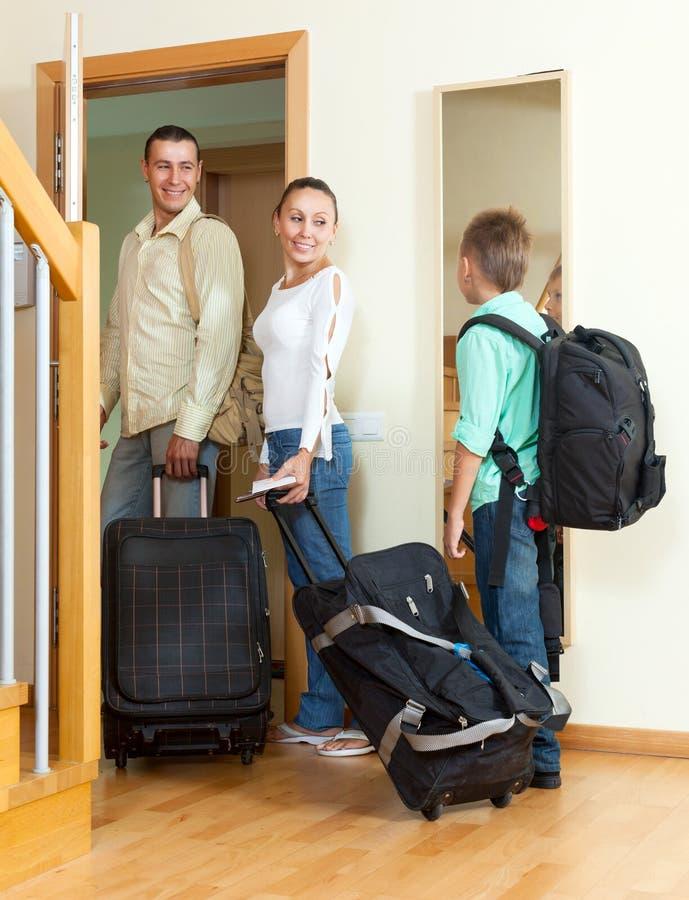 Vanlig familj av tre med bagage som ser i spegel nära doo royaltyfri bild