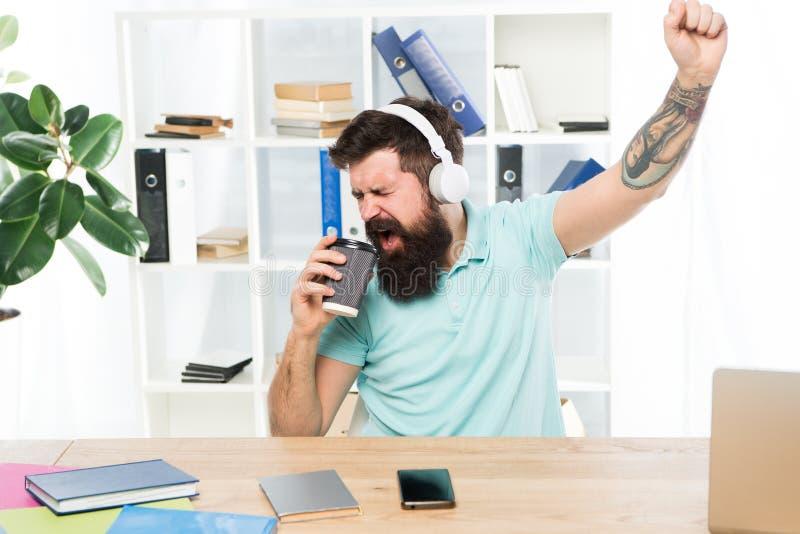 Vanlig kontorsdag Sitter den skäggiga grabbhörlurar för man kontoret lyssnar musik att sjunga sång Arbetaren med kaffekoppen börj arkivbild