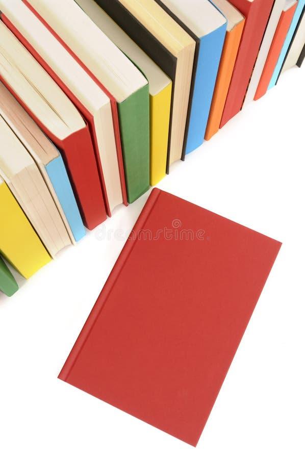 Vanlig röd bok med rad av färgrika böcker arkivfoto