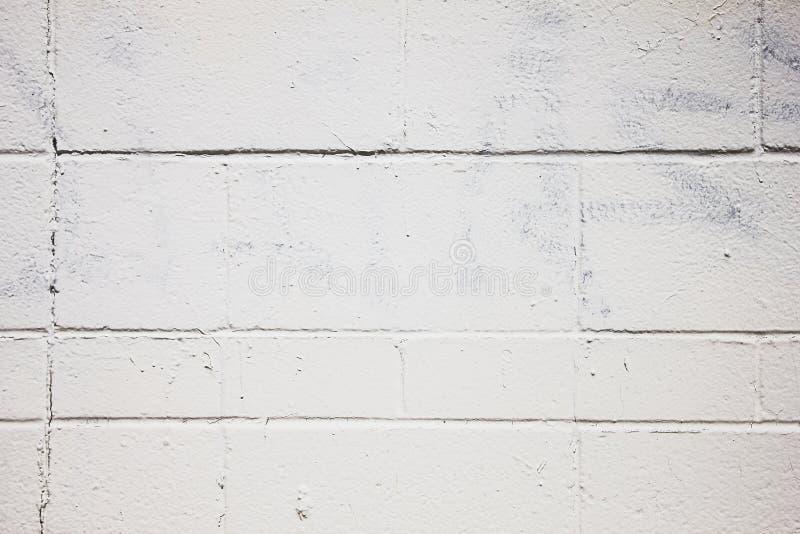 Vanlig vit vägg som göras ut ur Cinder Blocks med målat över Graffitti arkivbilder