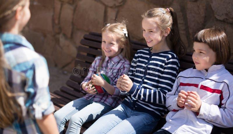 Vanliga barn i parkera på en bänk i höst fotografering för bildbyråer