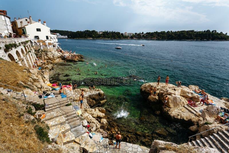 Vanno d'accordo le rocce per prendere il sole ed il salto in Rovigno, Croazia fotografie stock