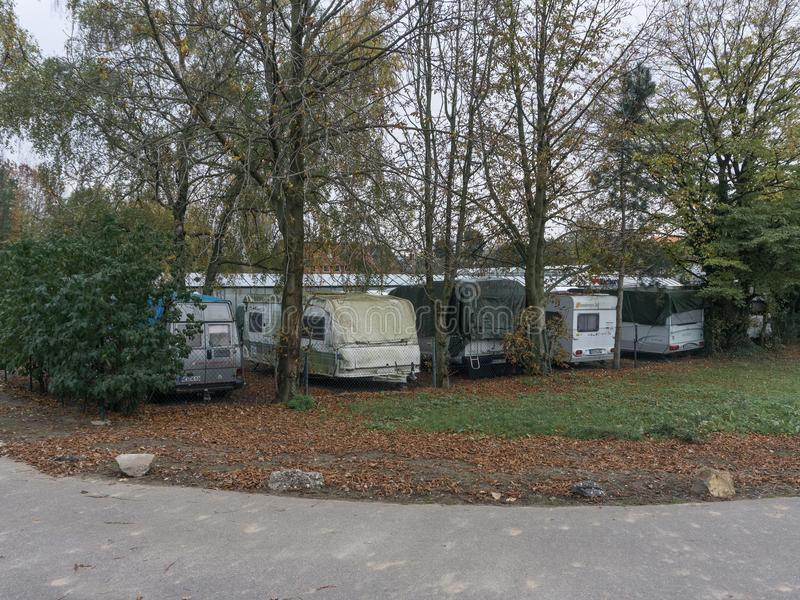Vans and trucks standing on a lawn covered with yellow autumn leaves. Vans and campers standing on the lawn among the trees, covered with yellow autumn leaves stock photo