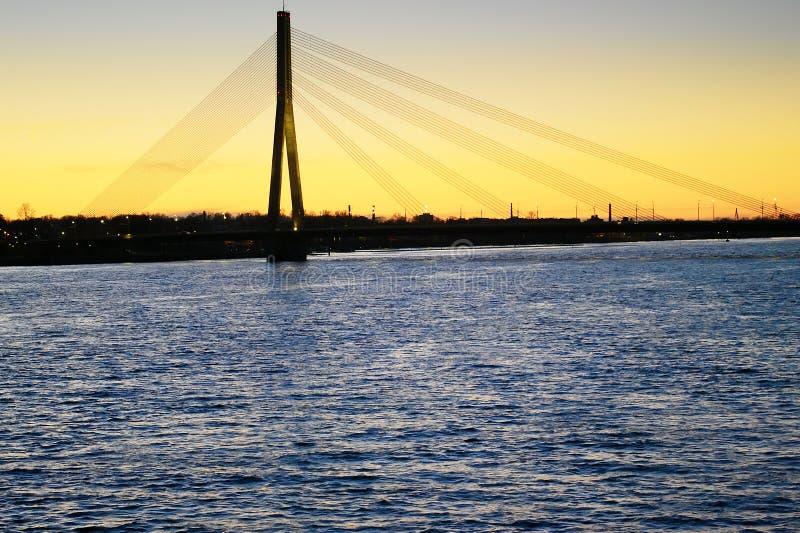 Vansu bro över Daugavafloden, västra Dvina, på solnedgången latvia riga royaltyfri fotografi