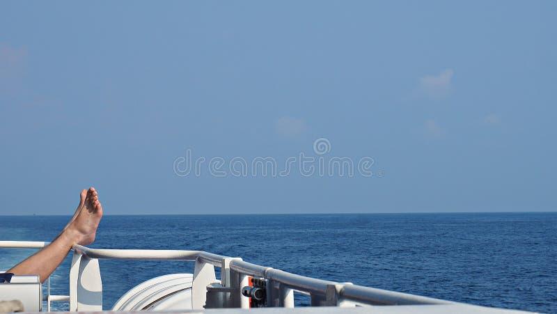 Vantaggi della donna sull'inferriata della barca con il fondo del mare e del cielo blu fotografia stock libera da diritti