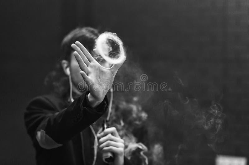 Vape人 年轻英俊的白人让圆环在从电子香烟的蒸汽外面 北京,中国黑白照片 图库摄影