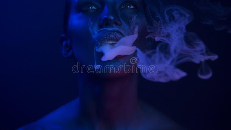 Vape党,夜生活 美好性感妇女抽烟 免版税库存照片