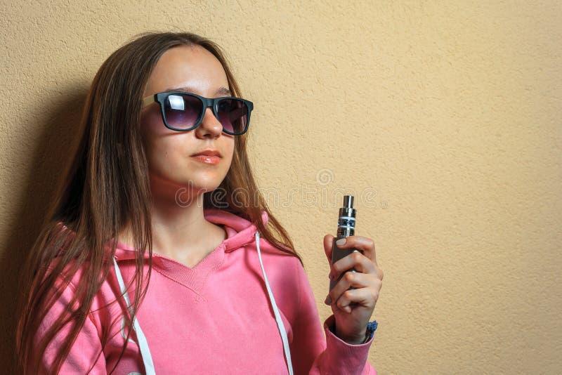 Vape女孩 年轻逗人喜爱的妇女画象桃红色有冠乌鸦和太阳镜的在她的手上的拿着一根电子香烟在赭色对面 免版税库存图片