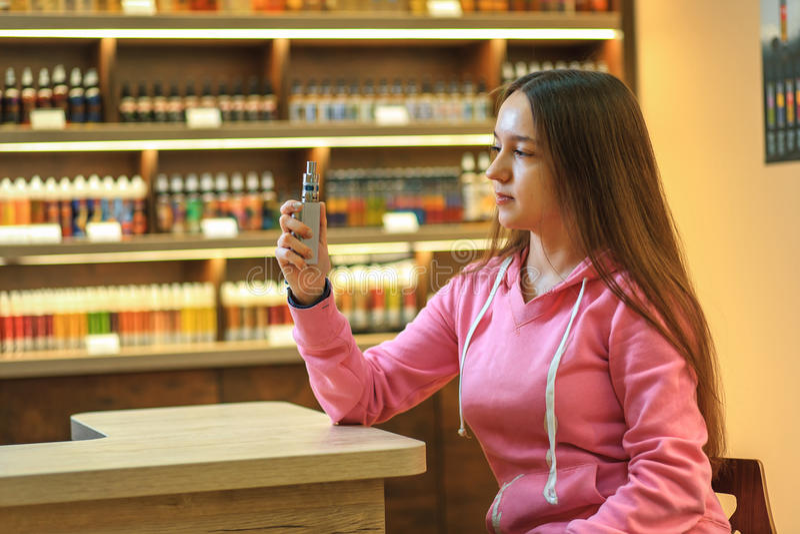 Vape妇女 抽一根电子香烟的桃红色有冠乌鸦的年轻逗人喜爱的女孩 免版税库存照片
