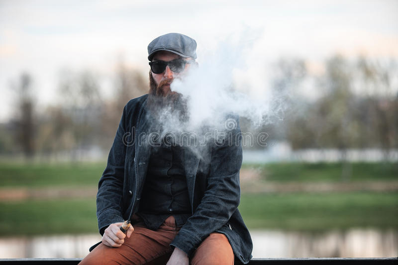 Vape有胡子的人在真正的生活中 年轻人画象有大胡子的在vaping一根电子香烟的盖帽和太阳镜 免版税库存图片