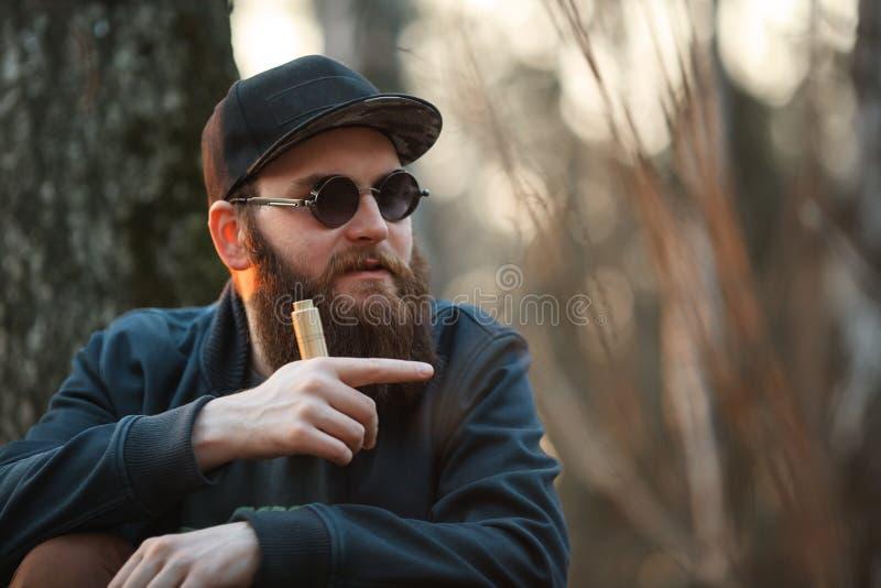 Vape Зверский молодой человек с огромной бородой в солнечных очках и крышке и с электронной сигаретой в древесинах на заходе солн стоковые изображения