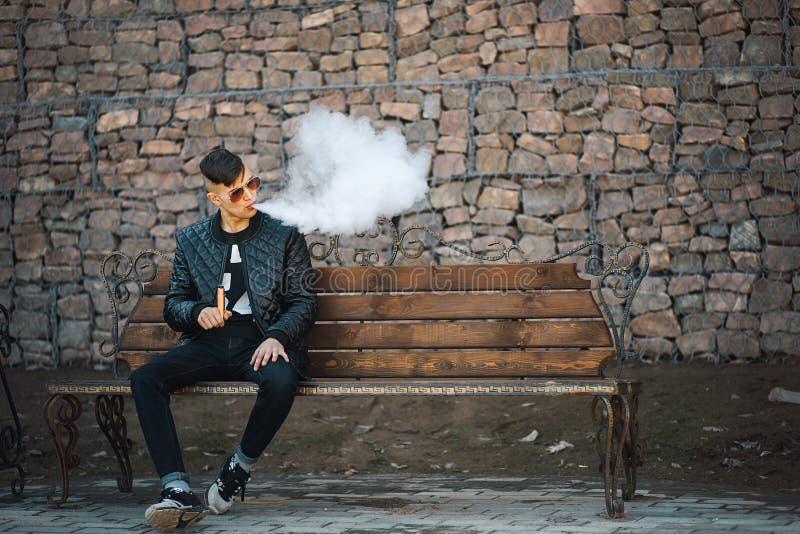 Vape 一个年轻英俊的人坐长凳并且吹从一根电子香烟的蒸汽 免版税库存照片